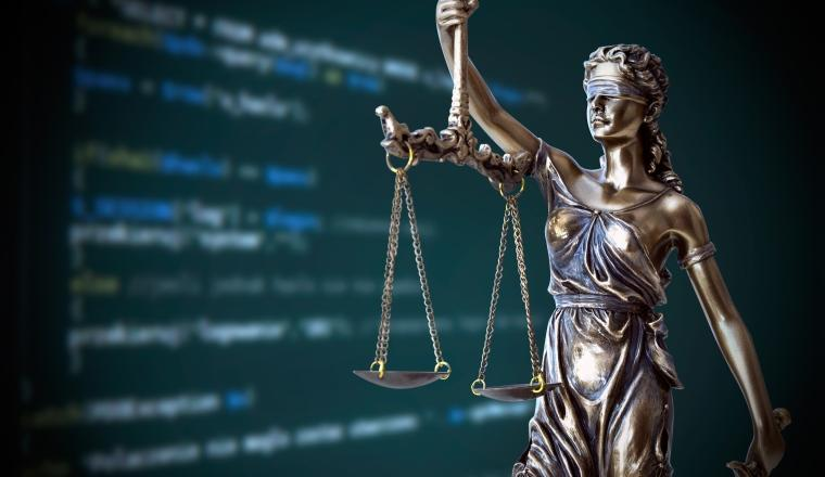 Scales of justice in front of a digital screen