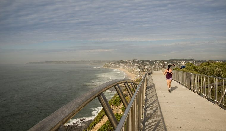 Woman jogging along the Newcastle Memorial Walk with the ocean and coastline on the left.