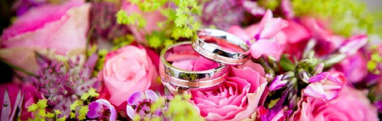 pair of wedding rings sitting on top of flowers