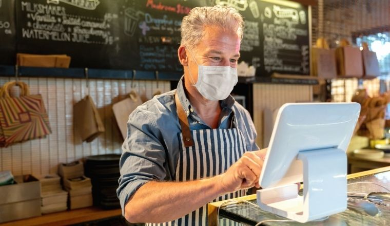 A business manager working at a cafe with a face mask on