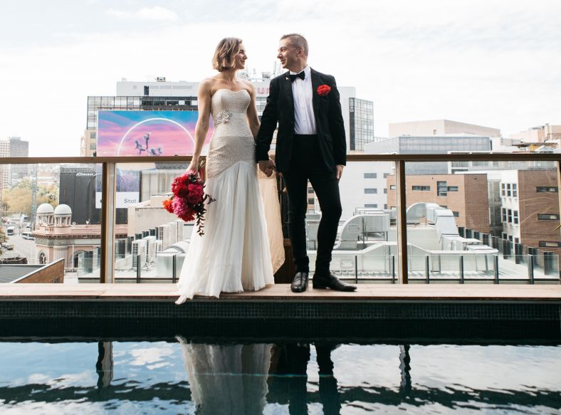 Couple celebrating their marriage on the roof top pool terrace at the Old Clare Hotel
